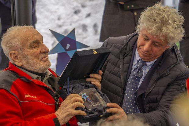"Cesare Maestri odbiera ""Genziana alla carriera"" z rąk Mauro Leveghi, dyrektora 67. Trento Film Festival (fot. mountainblog.it)"