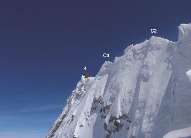 Dystans pomiędzy C2 a szczytem (4) to około 20 metrów w poziomie i trzy do sześciu w pionie, w zależności od warunków śniegowych. Ludzie w czerwonych kombinezonach znajdują się na właściwym wierzchołku (fot. Guy Cotter)